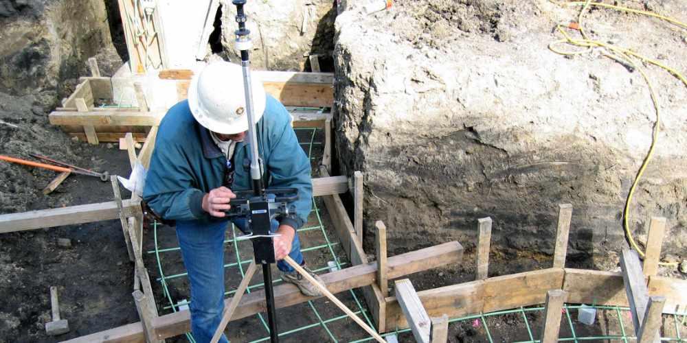 Surveyor assessing construction staking